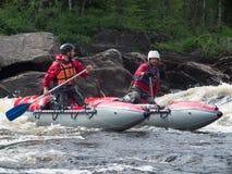 两个年轻人在手中坐有桨的一条可膨胀的小船 库存图片