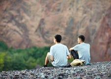 两个年轻人坐岩石峭壁 图库摄影