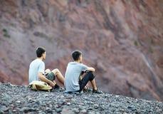 两个年轻人坐岩石峭壁 免版税库存照片