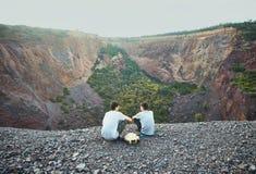 两个年轻人坐岩石峭壁 库存照片