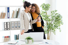 两个年轻人女实业家与手机一起使用在办公室 图库摄影