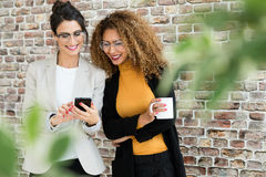 两个年轻人女实业家与手机一起使用在办公室 免版税库存图片