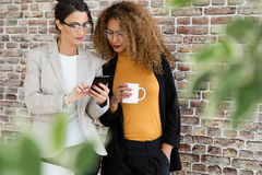 两个年轻人女实业家与手机一起使用在办公室 免版税图库摄影