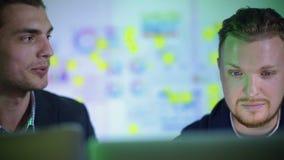 两个年轻人工作在办公室在晚上 股票录像