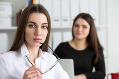 两个年轻人工作在他们的办公室的女商人 图库摄影