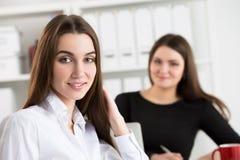两个年轻人工作在他们的办公室的女商人 免版税库存图片