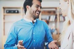 两个年轻人微笑在巨大讨论以后的商务伙伴在现代办公室 水平,被弄脏的背景 免版税库存照片