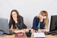两个年轻人疲倦地坐在书桌后的办工室职员 库存图片