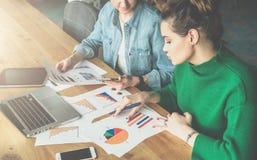 两个年轻人谈论的女商人坐在办公室在桌上和业务发展 免版税库存图片