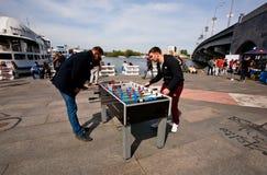 两个年轻人踢在露天街道节日的桌橄榄球 库存照片