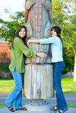 两个年轻人,两种人种的青少年的女孩在拥抱在su的公园标识杆 免版税图库摄影