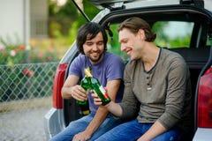 两个年轻人从瓶的饮料啤酒 图库摄影