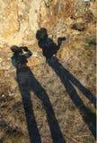 两个年轻人滑稽的树荫图在岩石 库存照片