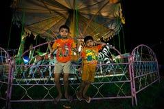 两个年轻印度尼西亚男孩使用在一个旅行的狂欢节在巴厘岛 免版税库存照片