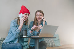两个年轻女商人坐在咖啡馆的桌上和谈话在手机,当观看在屏幕膝上型计算机时 免版税库存图片