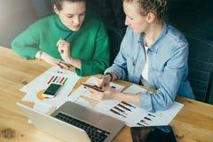 两个年轻女商人坐在膝上型计算机,智能手机,片剂计算机的桌上的,纸张文件,图表 库存照片