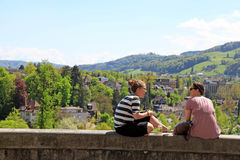 两个年轻女学生坐栏杆。 库存图片