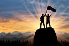 两个登山人剪影在山上面的与一面旗子在他的手上 免版税库存照片