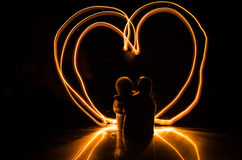 两个年轻恋人绘在火的心脏 夫妇和爱词剪影在黑暗的背景 库存图片
