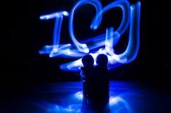两个年轻恋人绘在火的心脏 夫妇和爱词剪影在黑暗的背景 免版税库存图片