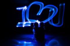 两个年轻恋人绘在火的心脏 夫妇和爱词剪影在黑暗的背景 库存照片