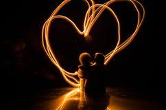 两个年轻恋人绘在火的心脏 夫妇和爱词剪影在黑暗的背景 免版税图库摄影