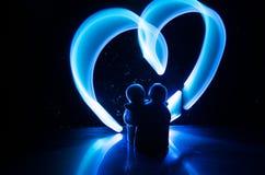 两个年轻恋人绘在火的心脏 夫妇和爱词剪影在黑暗的背景 免版税库存照片
