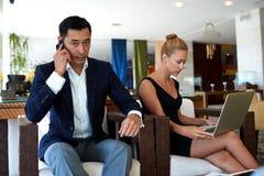 两个年轻成功商人繁忙工作在现代办公室空间,当为见面做准备时 免版税库存图片