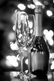 两个玻璃和瓶反对圣诞灯的香宾 库存照片