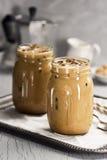 两个玻璃瓶子与奶油的被冰的咖啡 图库摄影