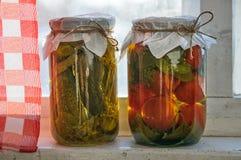 两个玻璃瓶子在窗台的五颜六色的泡菜 库存图片