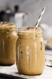 两个玻璃瓶子用被冰的咖啡用牛奶 免版税库存照片