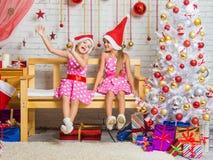 两个滑稽的女孩唬弄坐在圣诞节设置的一条长凳 图库摄影