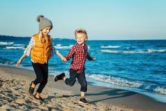两个滑稽的白白种人孩子画象哄骗演奏跑在海洋在日落的海海滩的朋友 免版税图库摄影