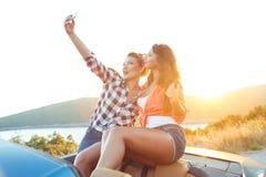 两个年轻美丽的女孩做着在敞篷车的selfie 免版税库存照片
