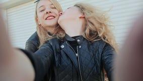两个年轻美丽的女朋友白肤金发的乐趣和卖弄风情摆在照相机前面 做selfie 春天 影视素材
