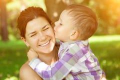 两个绿色牛仔裤妈妈儿子顶层佩带 孩子亲吻他的自然背景的母亲 假定 库存图片