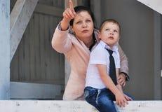 两个绿色牛仔裤妈妈儿子顶层佩带 库存照片