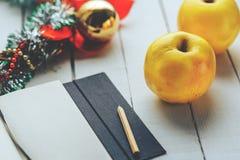 两个黄色苹果、笔记本有铅笔的和圣诞节装饰在白色木头 免版税库存照片