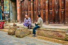 两个年迈的人在街道,加德满都,尼泊尔谈论 免版税图库摄影