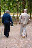两个年长人步行沿着向下街道 免版税库存图片