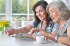 两个年长女朋友读一本杂志 库存照片
