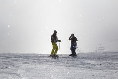 两个滑雪者拍在有薄雾的滑雪倾斜的照片 库存照片