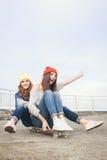 两个年轻longboarding的女朋友 免版税库存照片