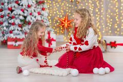 两个beautyful逗人喜爱的女孩微笑的姐妹朋友和xmas豪华绿色白色树圣诞节画象在独特的内部演播室 库存图片