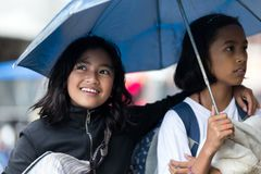 两个Filiapina女孩在伞下 免版税库存图片