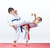 两个karateka孩子打反撞力腿 免版税库存照片