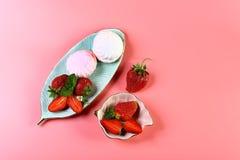 两个platesof蛋白软糖和新鲜的草莓,隔绝在与拷贝空间的桃红色背景 看法从上面,集合 库存照片