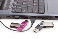 两个USB闪光驱动和USB缚住反对膝上型计算机 库存照片