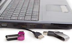 两个USB闪光驱动和USB缚住反对膝上型计算机 库存图片